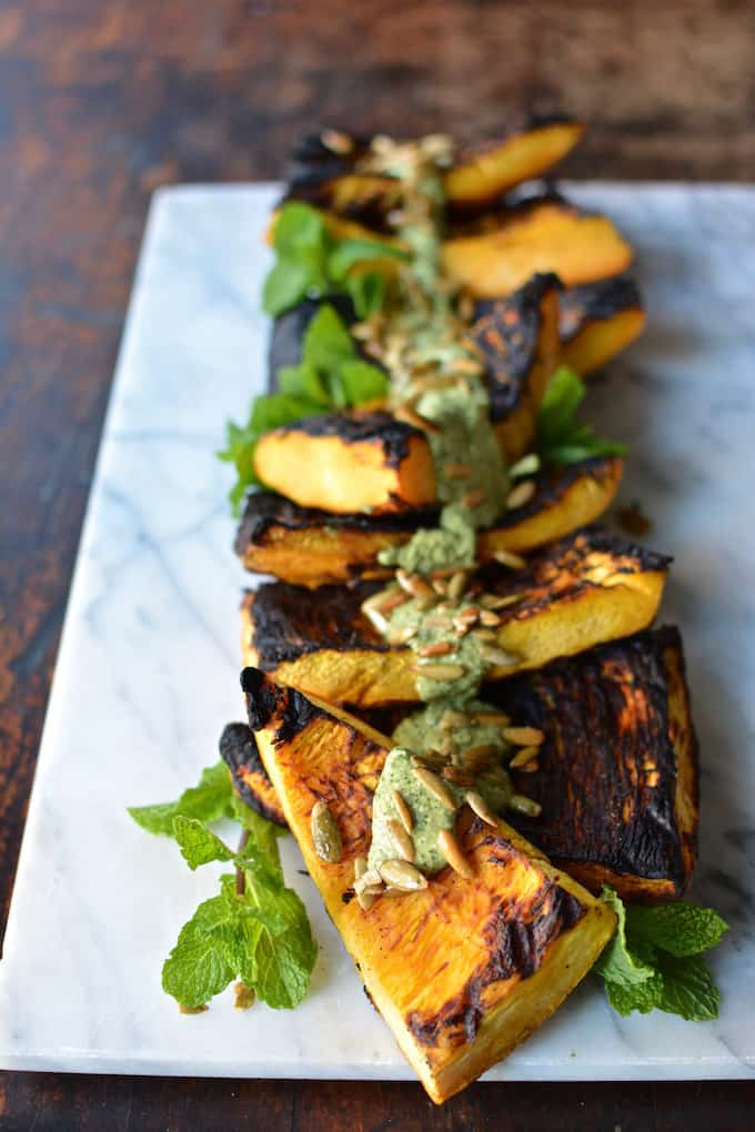 Grilled pumpkin steaks are an excellent way to eat up that delicious Halloween Jack-O-Lantern with creamy black beans and spicy jalapeño pesto sauce! Healthy Latin food, Latin recipe, pumpkin recipe, vegan recipe. #healthylatinrecipe #latinrecipe #pumpkinrecipe #veganrecipe