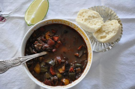 Overhead shot of a bowl of black bean and vegetable chili with a corn muffin and a cut lime wedge.