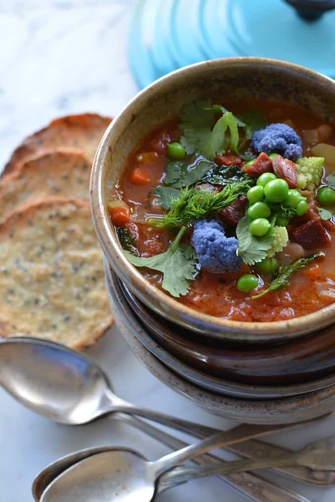 Chorizo, Pinto Bean, and Potato Minestrone is a Latin-inspired version of the traditional Italian soup. Filled with spring vegetables like sweet peas, purple cauliflower, and dill it is perfect for warming up those damp spring nights. #minestrone #healthyMexican #healthysoup