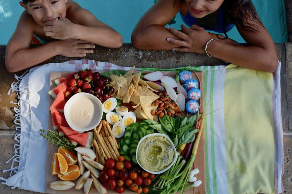 Two kids in a swimming pool standing next to a platter of snacks like fresh fruit and vegetables.