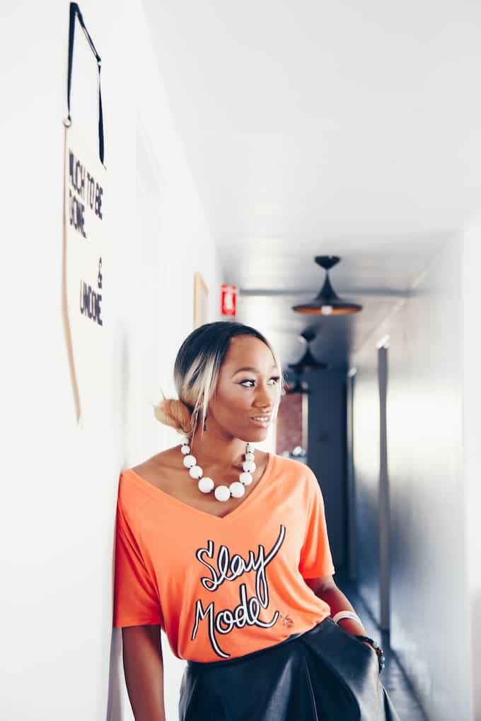 """A woman standing in a hallway leaning against a wall with an orange shirt that says """"Slay Mode"""" on it and a white beaded necklace."""