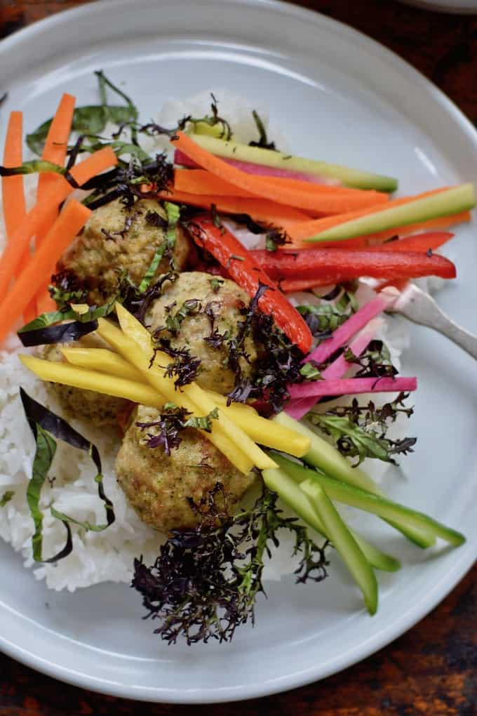 These Green Chili Chicken Meatballs do double duty as a healthy dinner served with steamed rice, a rainbow of crunchy vegetables and a sweet and spicy dipping sauce, then leftovers get tucked into lettuce cups for tomorrow's lunch box! #chicken #chickendinner #chickenmeatballs