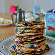 #ad  Celebrate spring with a tall stack of blueberry coconut banana pancakes! Made with Juicy Juice 100% Berry juice, coconut milk, blueberries, and coconut. #juicyjuice #blueberrypancakes #dairyfreepancakes #coconutpancakes #bananapancakes #pancakes