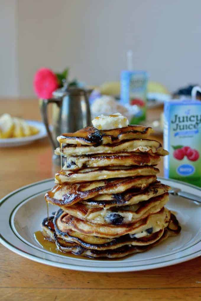 #ad| Celebrate spring with a tall stack of blueberry coconut banana pancakes! Made with Juicy Juice 100% Berry juice, coconut milk, blueberries, and coconut. #juicyjuice #blueberrypancakes #dairyfreepancakes #coconutpancakes #bananapancakes #pancakes