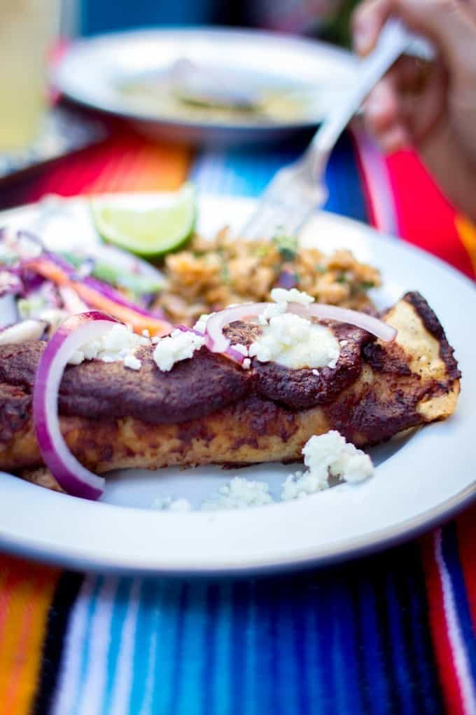 An enchilada covered in a purple sauce sitting on a plate with red onion slices and crumbled cheese on top. The plate in on a colorful table cloth.