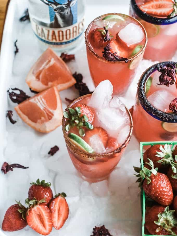 What kind of tequila should you use for Palomas? Click here to find out and get this Strawberry Hibiscus Paloma is the essence of summer: Fresh grapefruit juice, floral hibiscus syrup, fragrant strawberries, lime juice, and tequila. #paloma #tequila #ad #tequilacazadores #tequilacocktails #holajalapeno