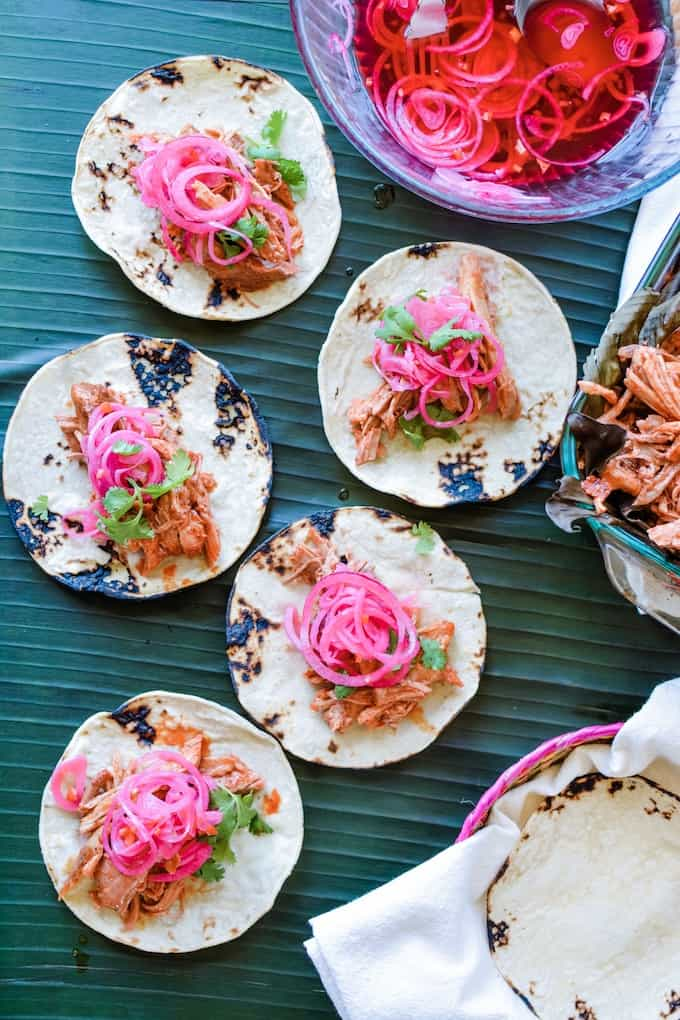 Toasted corn tortillas hold Cochinita Pibil tacos topped with red onions sitting on banana leaves.