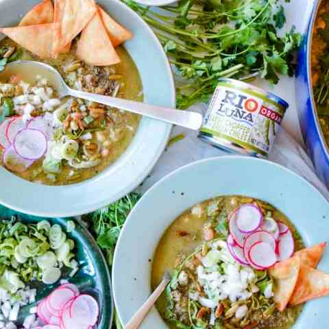 Two bowls of vegan pozole with spoons in them.