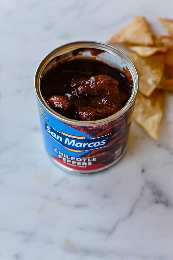 A can of San Marcos chipotle Peppers in Adobo Sauce sitting on a marble table with a few tortilla chips behind it.