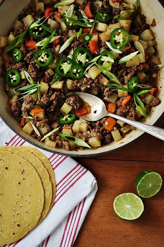 A pan of Picadillo topped with jalapeño slices and scallions sitting on a wooden table with tortillas next to it.