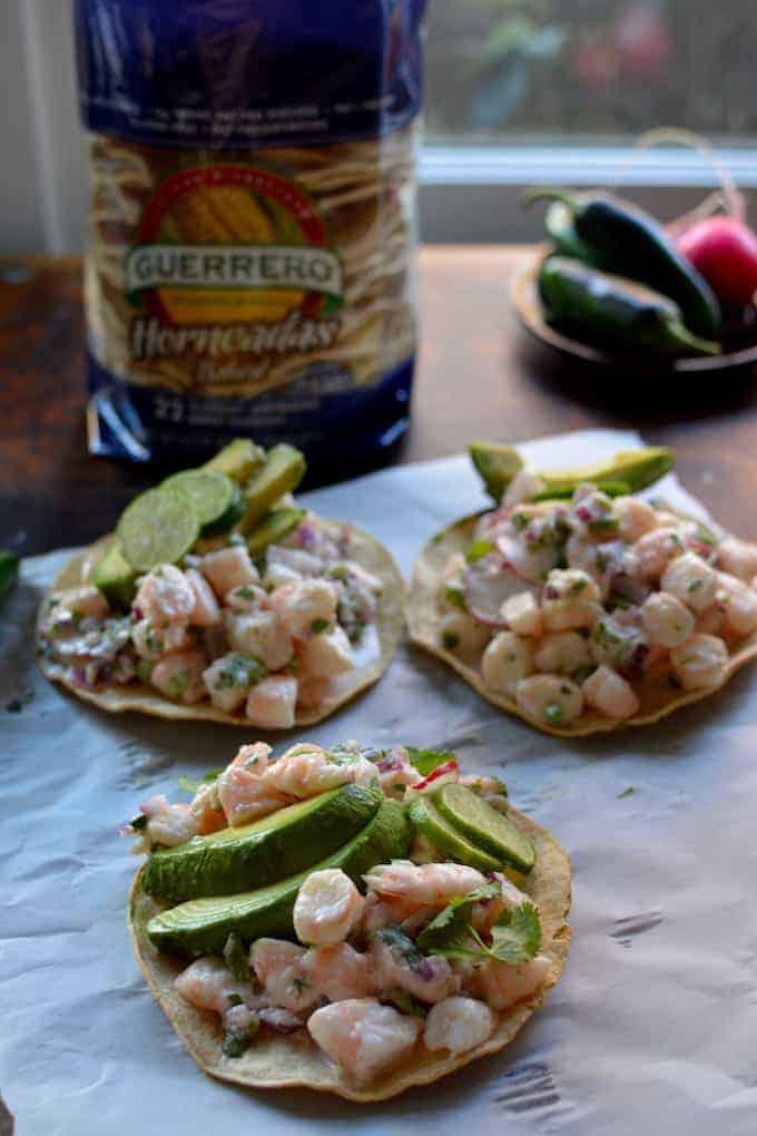 A super easy, ultra healthy shrimp ceviche tostada recipe with fresh squeezed lime juice, coconut milk, chiles, cilantro, and thinly sliced scallions.One of our most loved Mexican food recipes and exactly what we want at our quiet Cinco de Mayo celebration. Get all our ideas for a Stay-At-Home Cinco de Mayo party.  #cincodemayo #shrimp #ceviche #mexicanrecipes