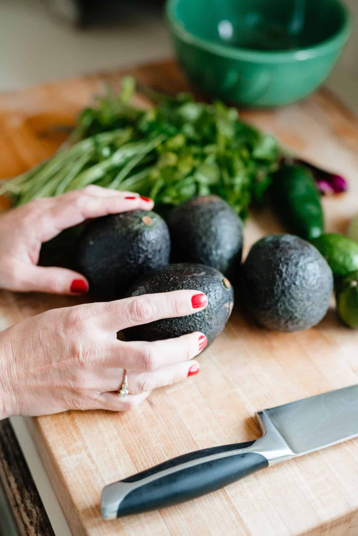 A woman's hands setting avocados on a wooden cutting board.