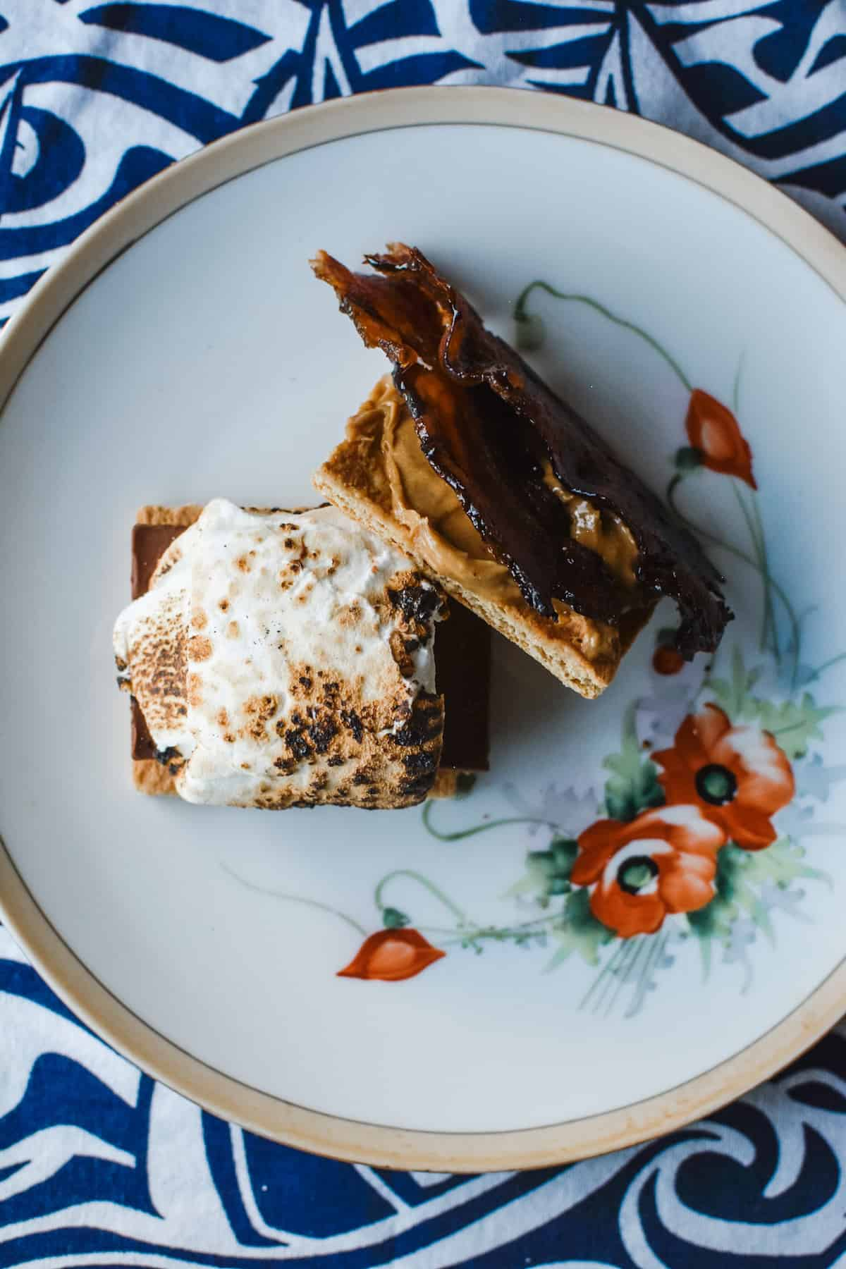 A s'more with peanut butter and candied bacon sitting on a floral plate on a blue and white cloth.