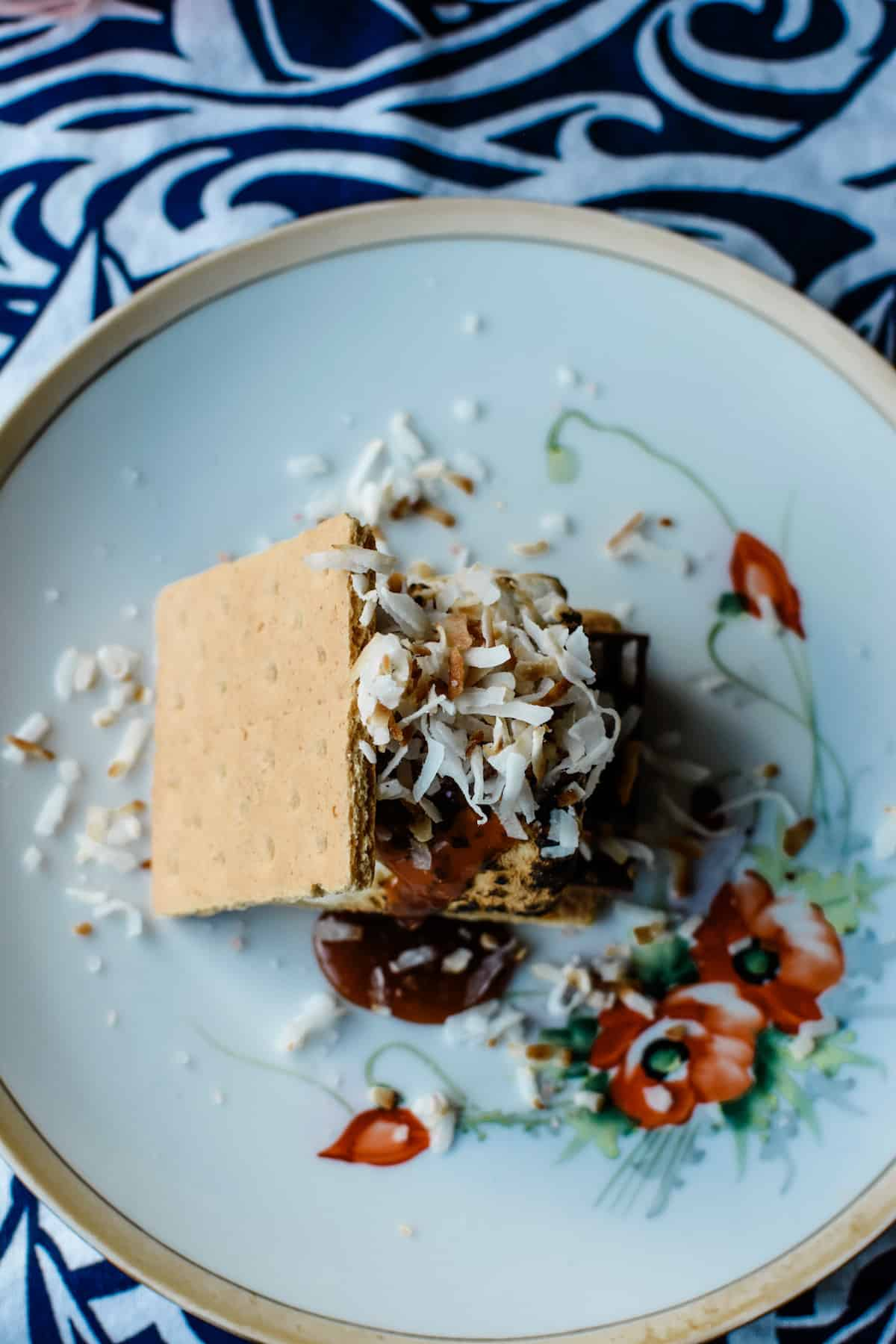 A s'mores dessert topped with toasted coconut sitting on a white plate with red flowers on it.