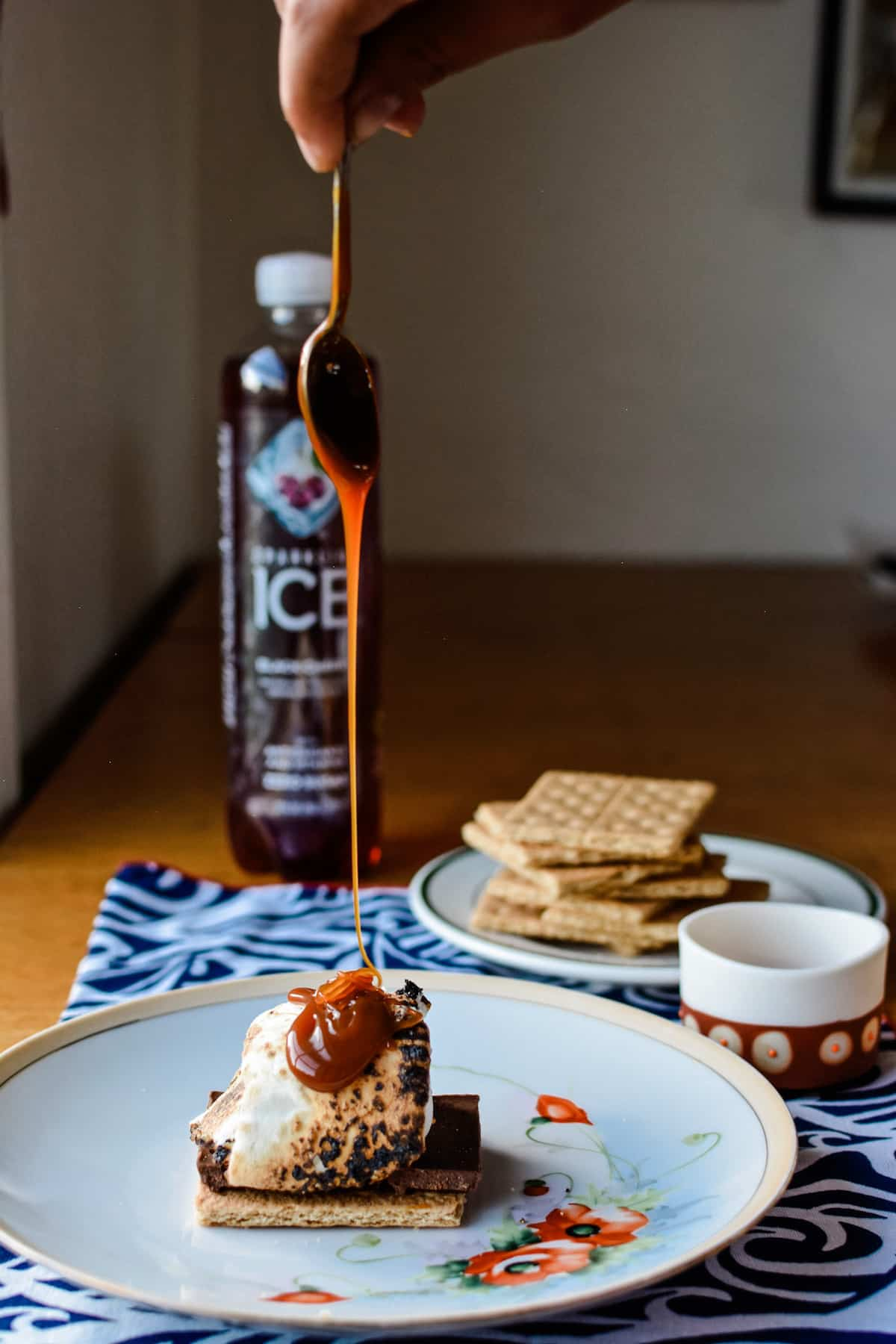 A graham cracker sitting on a white plate with chocolate and toasted marshmallow and a hand dripping caramel sauce on top.
