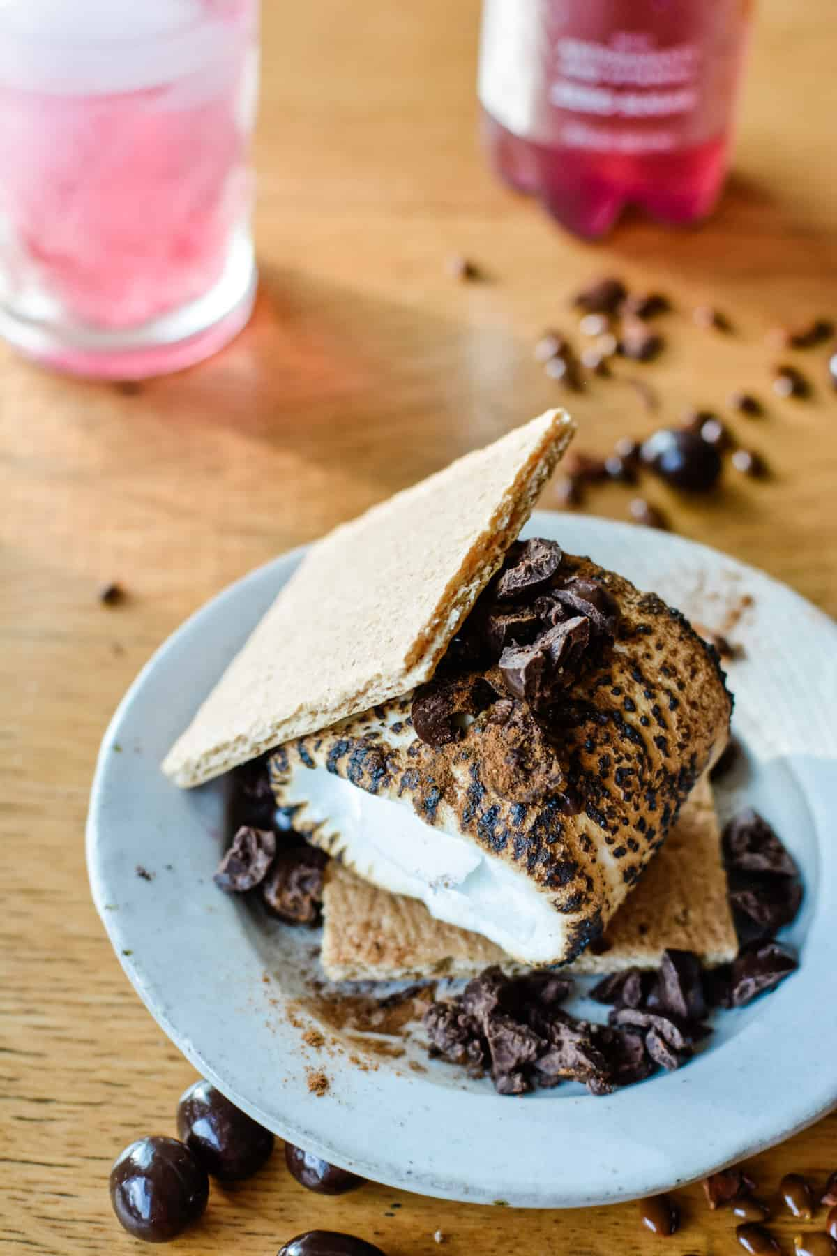 A s'mores dessert topped with chopped chocolate covered espresso beans and ground cinnamon sitting on a small plate on a wood table.