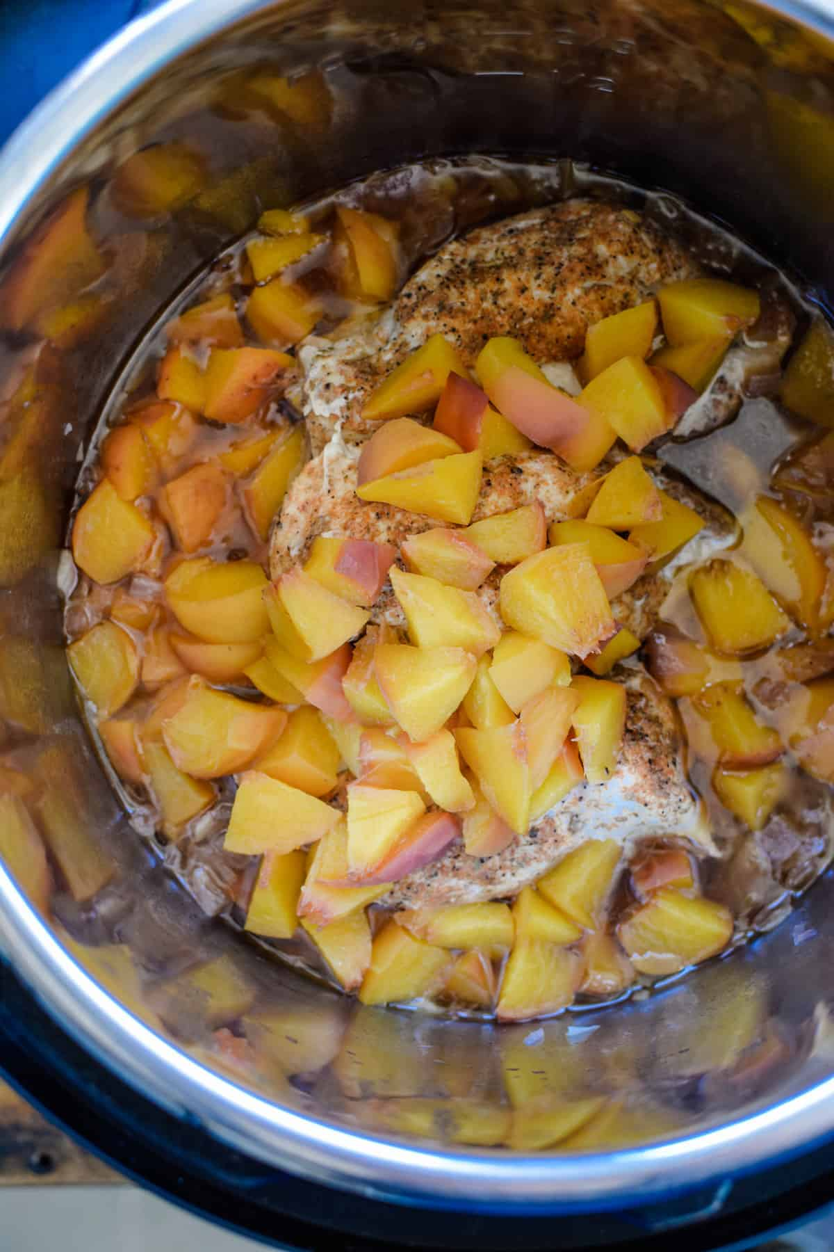 Peaches and chicken in a metal pot with liquid.
