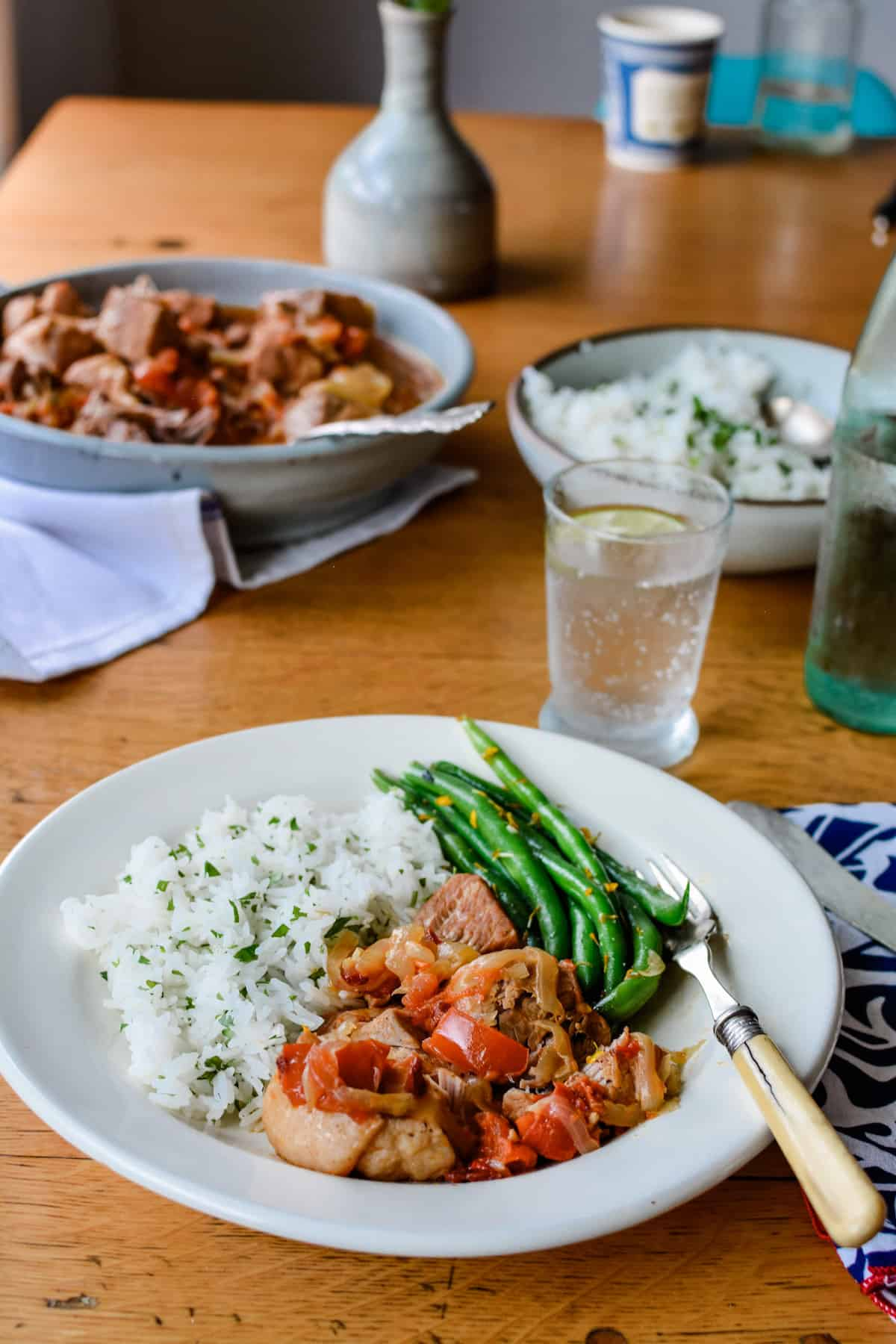 A plate of pork Tinga, white rice, and green beans sitting on a wood table with a fork on the plate, a blue and white napkin beside the plate.