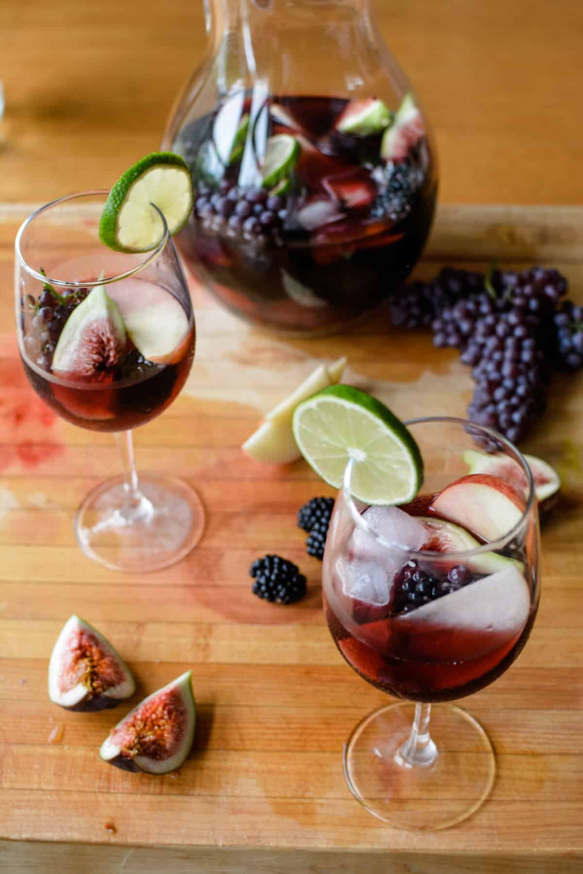 Two glasses filled with ice, fruit, and red wine sitting on a wood cutting board next to quartered figs and blackberries.