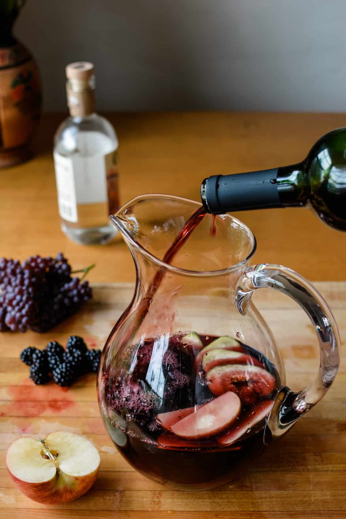 A pitcher with cut fruit in it and a bottle of red wine being poured into the pitcher.