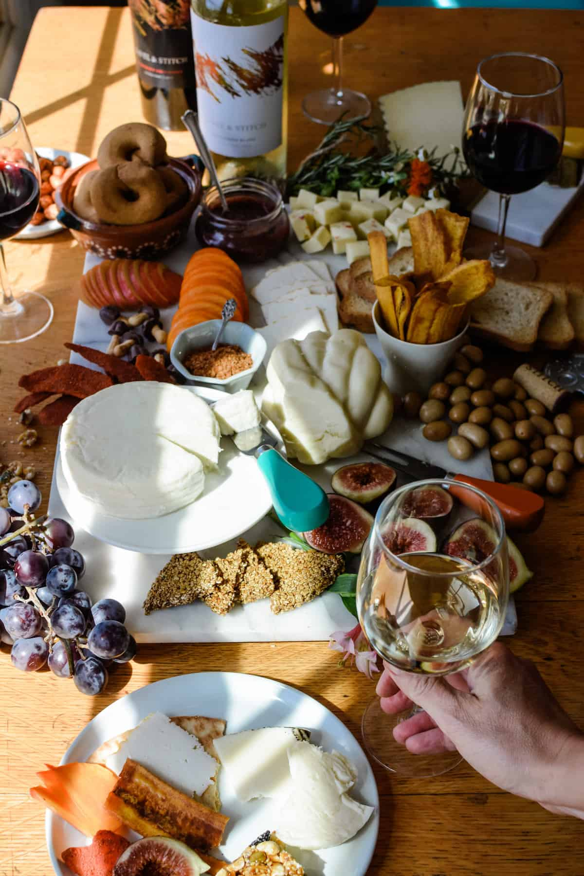 A wooden table filled with a Mexican Cheese Board filled with fruits, cheese, nuts, and glasses of wine plus bottles of wine around the table.