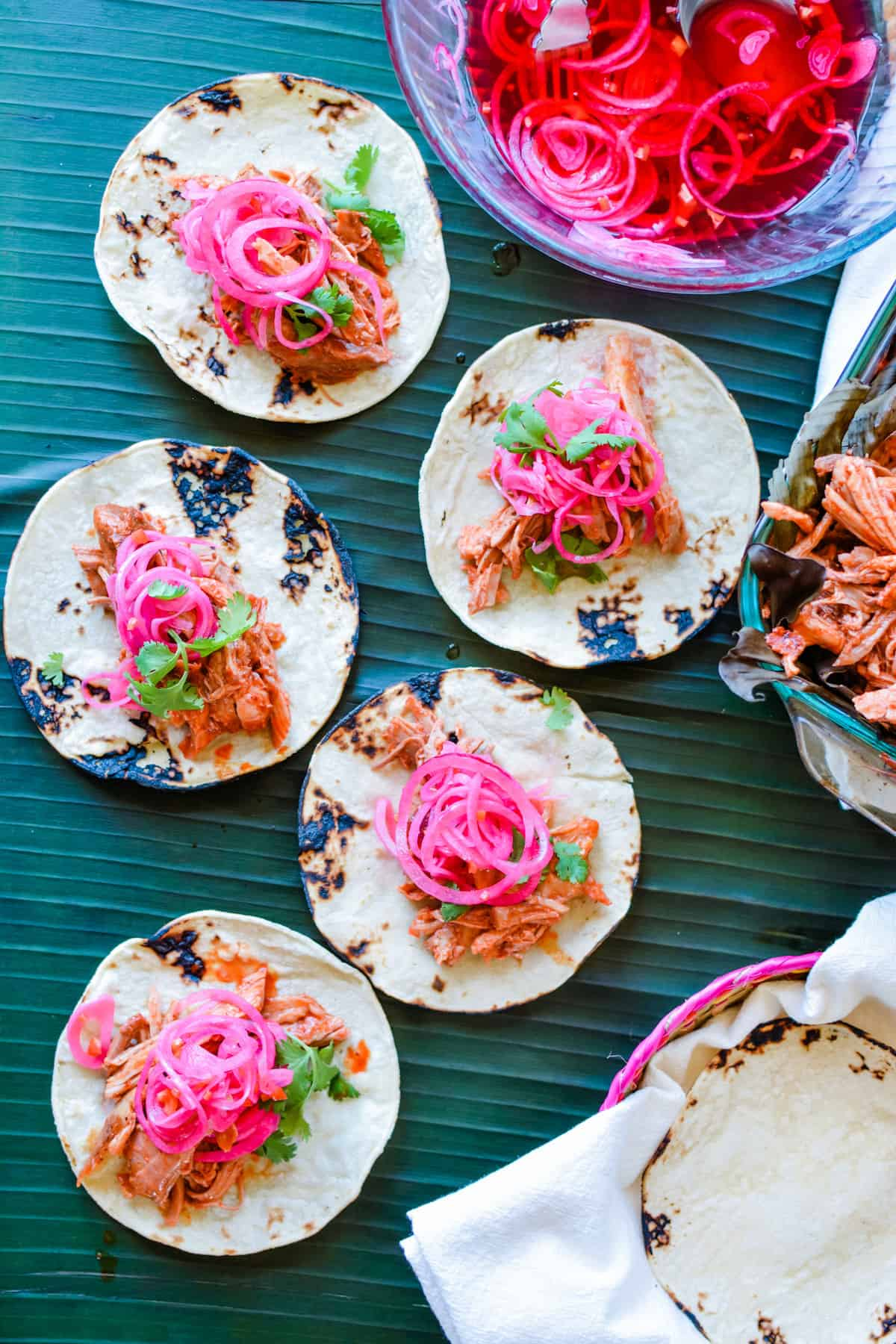 Five pork tacos with pickled red onions on top sitting on a green banana leaf with a bowl of pickled red onions next to them.
