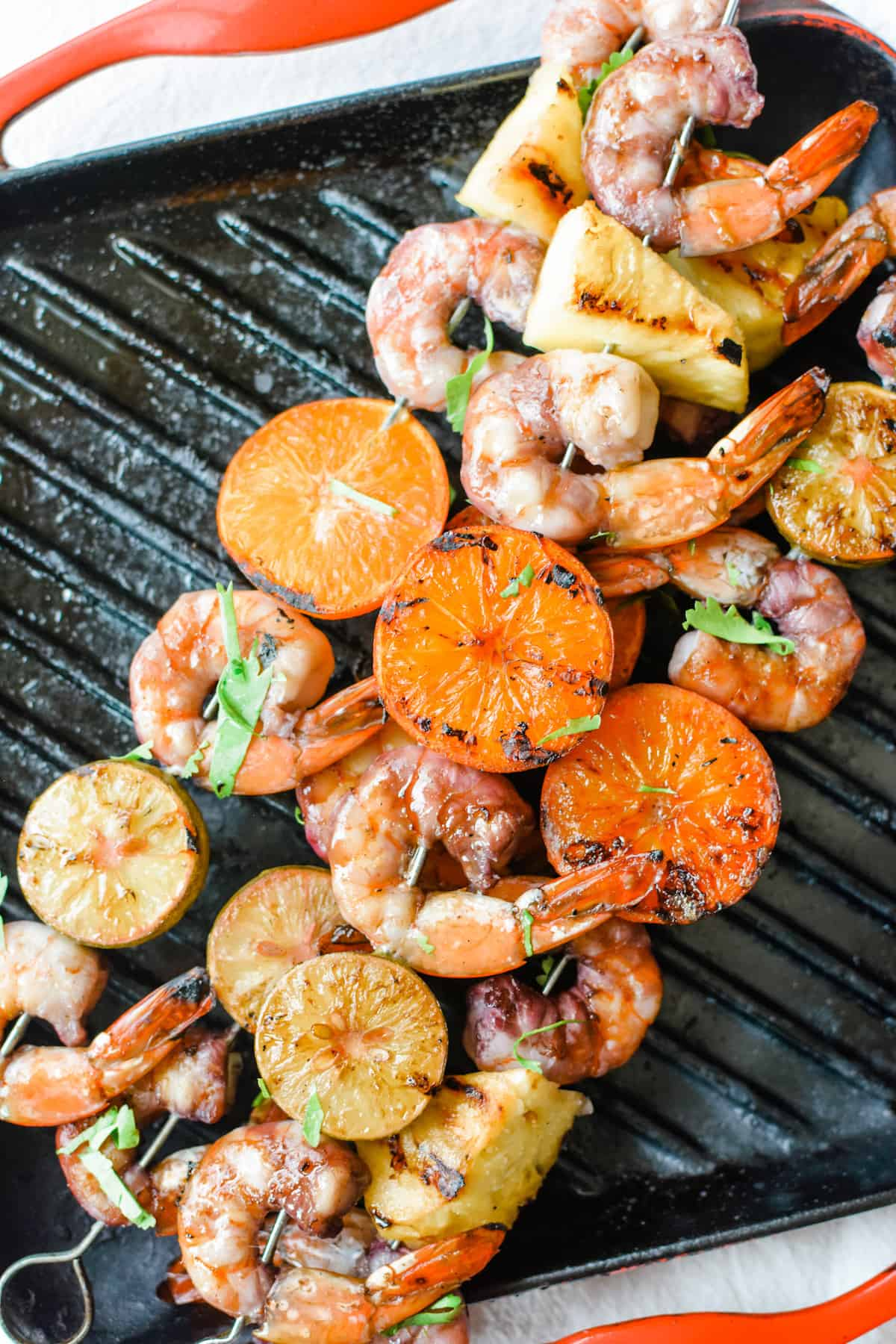 Overhead image of grilled shrimp, tangerine halves, key limes, and pineapple on metal skewers sitting on a grill pan with red edges.