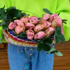 Girl in green sweater and jeans holding a basket of strawberry tamales.