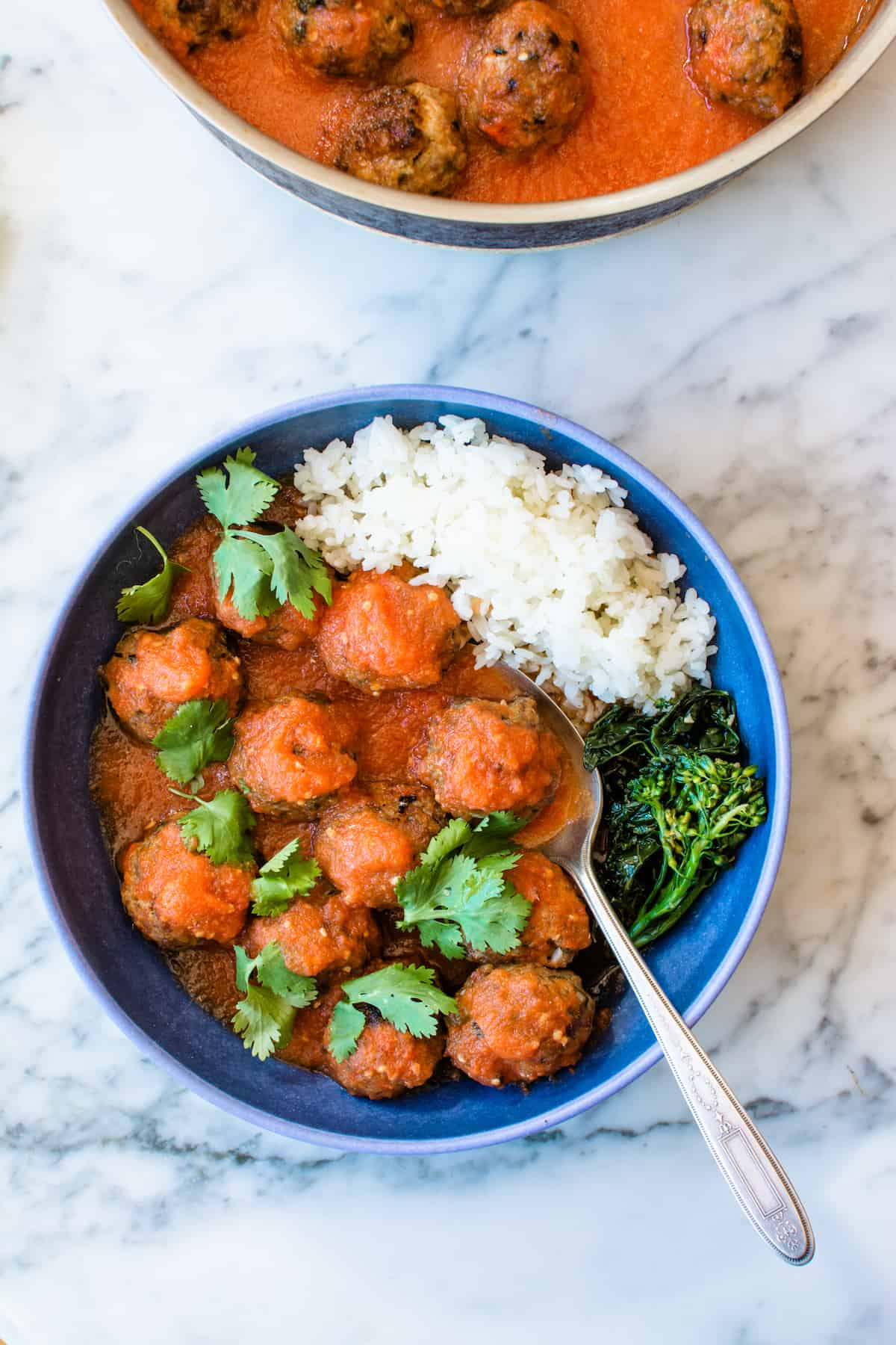 Overhead image of a bowl of albondigas with rice and green vegetables sitting on a marble table with a spoon in the bowl.