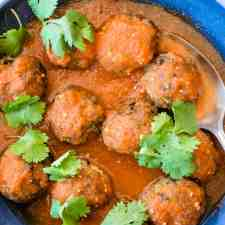 Overhead image of a blue bowl of pork albondigas in a arbol Chile sauce with cilantro leaves on top and a spoon in the bowl.