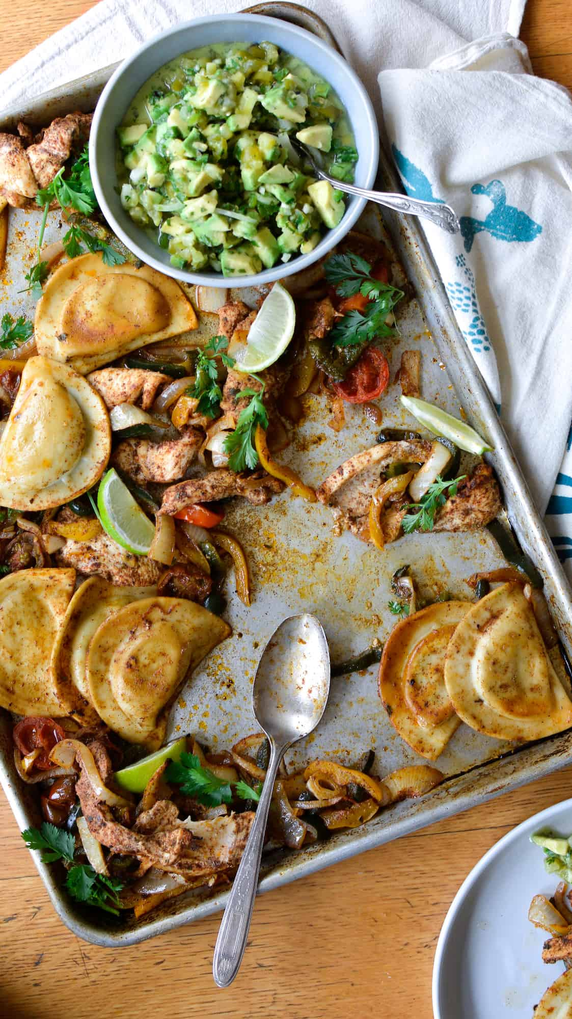 Overhead image of a baking sheet with strips of chicken, peppers, Pierogies, lime wedges, and a bowl of avocado salsa on it.