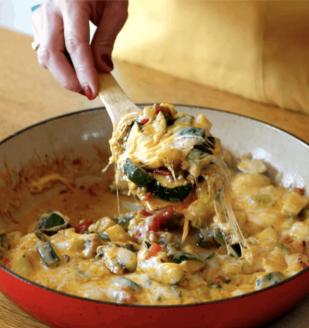 A red pan full of Calabacitas a Mexican side dish of squash covered with cheese with a hand spooning some of it out.