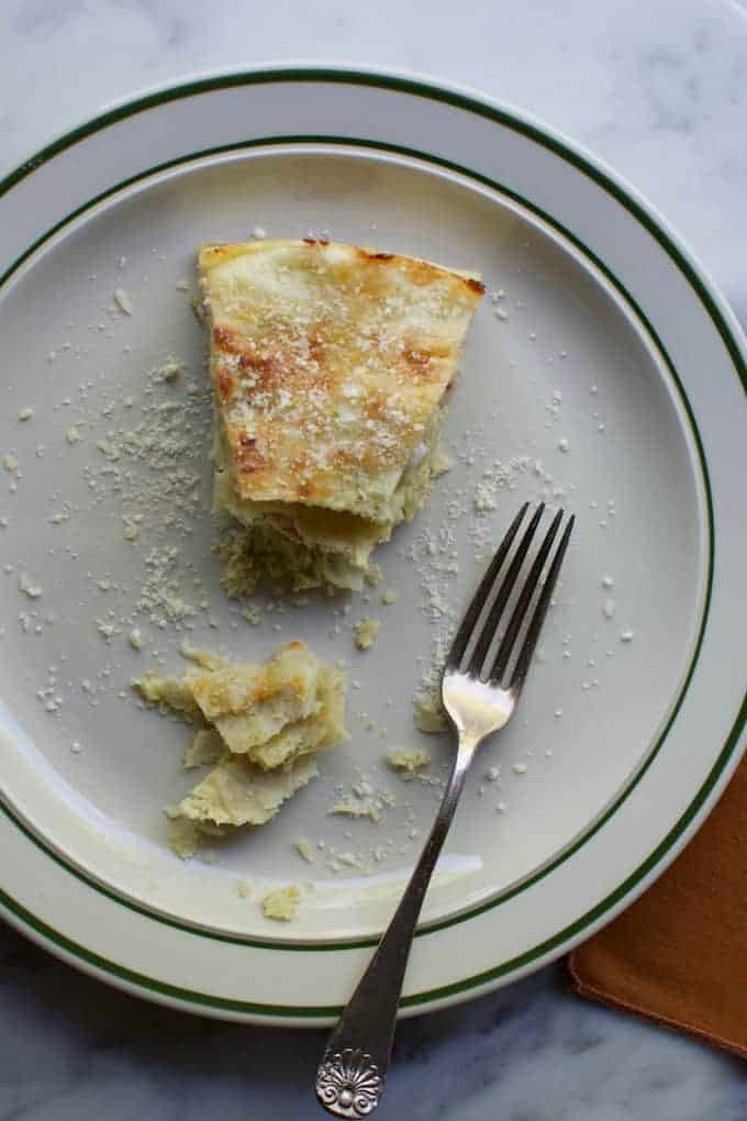 Overhead image of a slice of Stacked Chicken Enchiladas Suizas  on a white plate with a bite taken out and a fork on the plate.