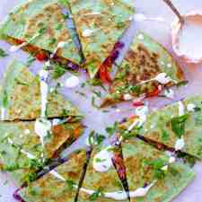 Overhead image of a veggie quesadilla on a cutting board with a pink little bowl of sour cream on the side.