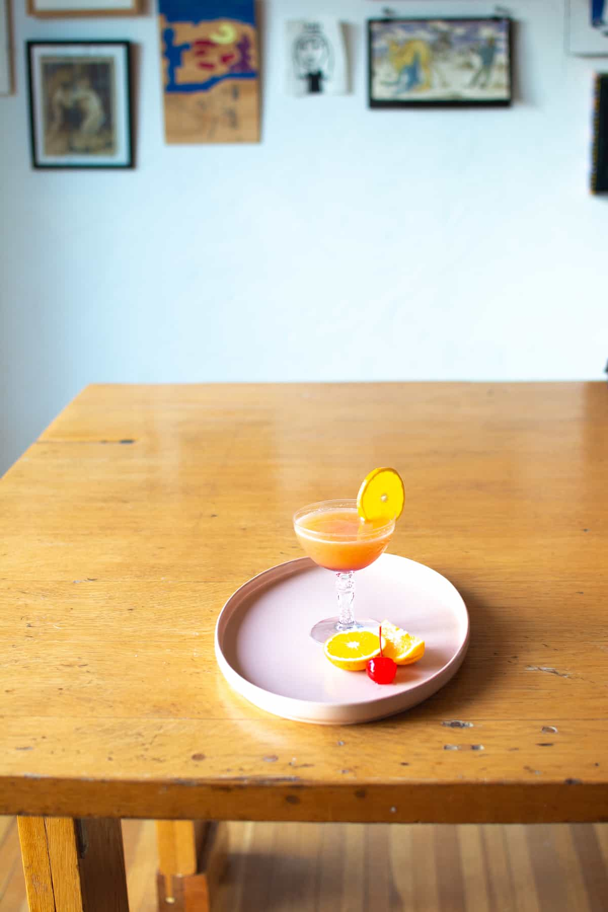 A tequila sunrise cocktail sitting on a pink plate with an orange and cherry on the plate.