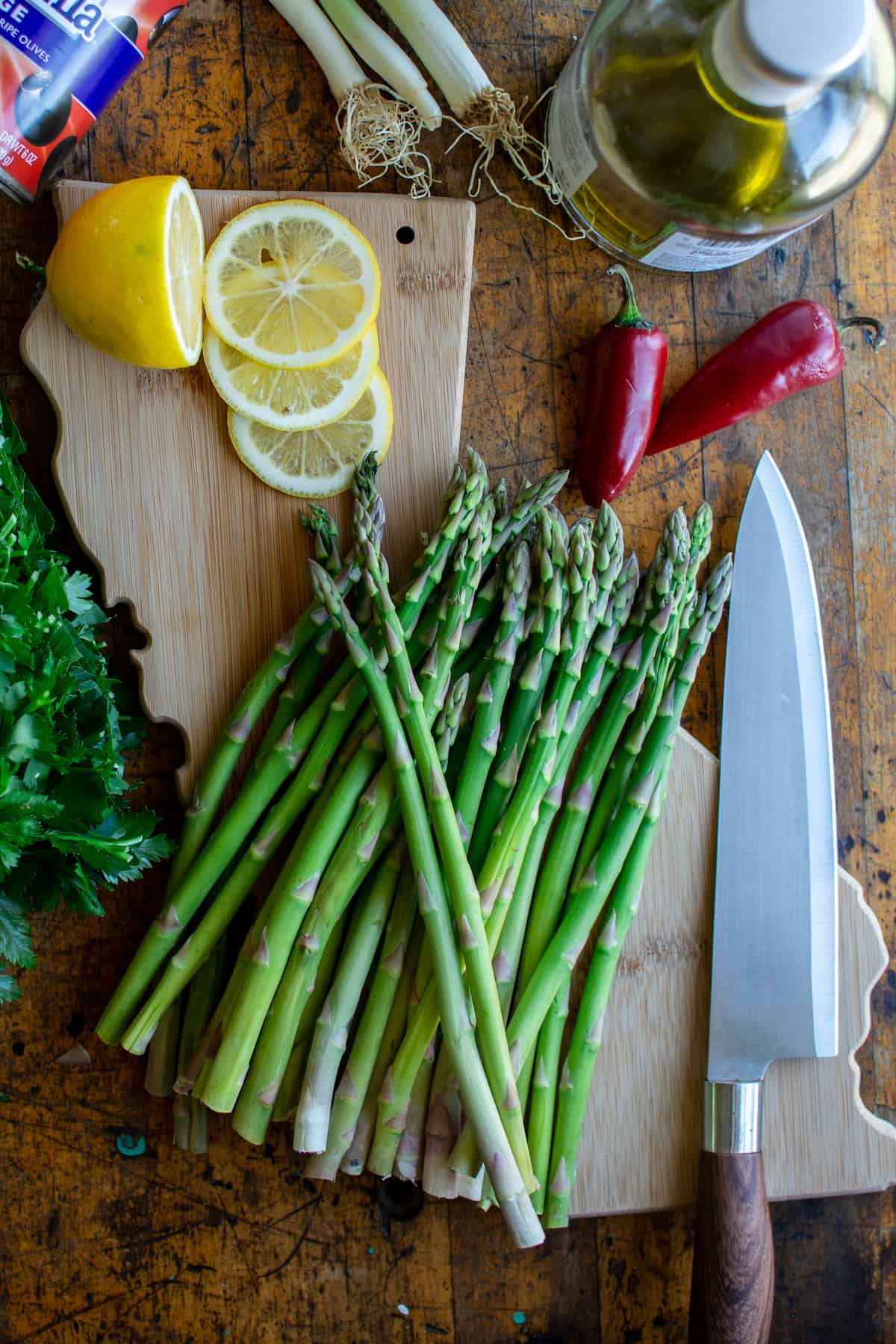 Overhead images of raw asparagus on a wood cutting board in the shape of California with a knife next to them and a lemon sliced above it.