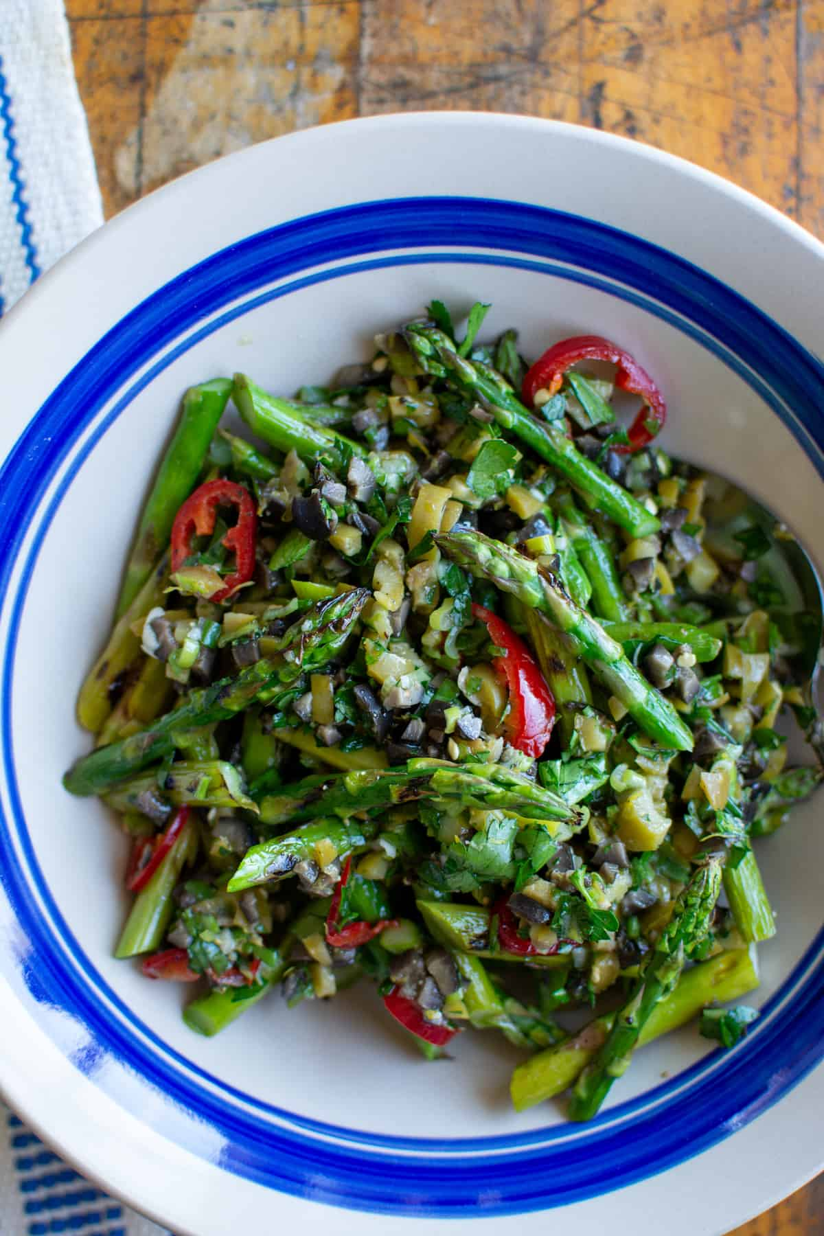 Overhead image of asparagus salad in a white bowl with a blue stripe sitting on a wood table.