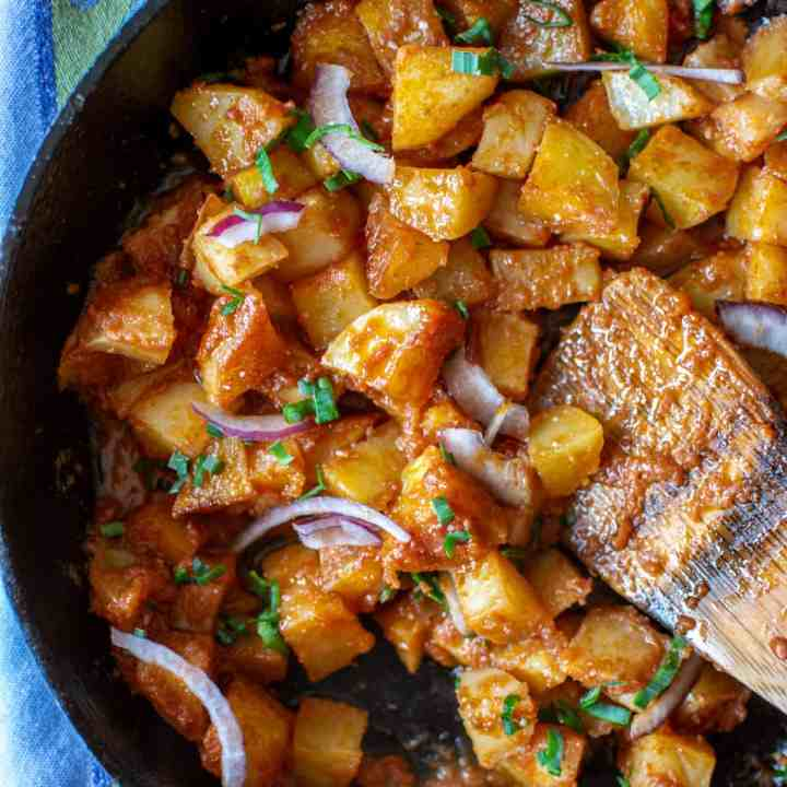 Papas con Chile is a simple, delicious vegan and gluten-free dish made with crispy fried potatoes cooked in a fresh tomato sauce with jalapeños. Enjoy as a side for breakfast or stuffed into tacos. #papasconchile #potatoes #mexicanfood #sidedish