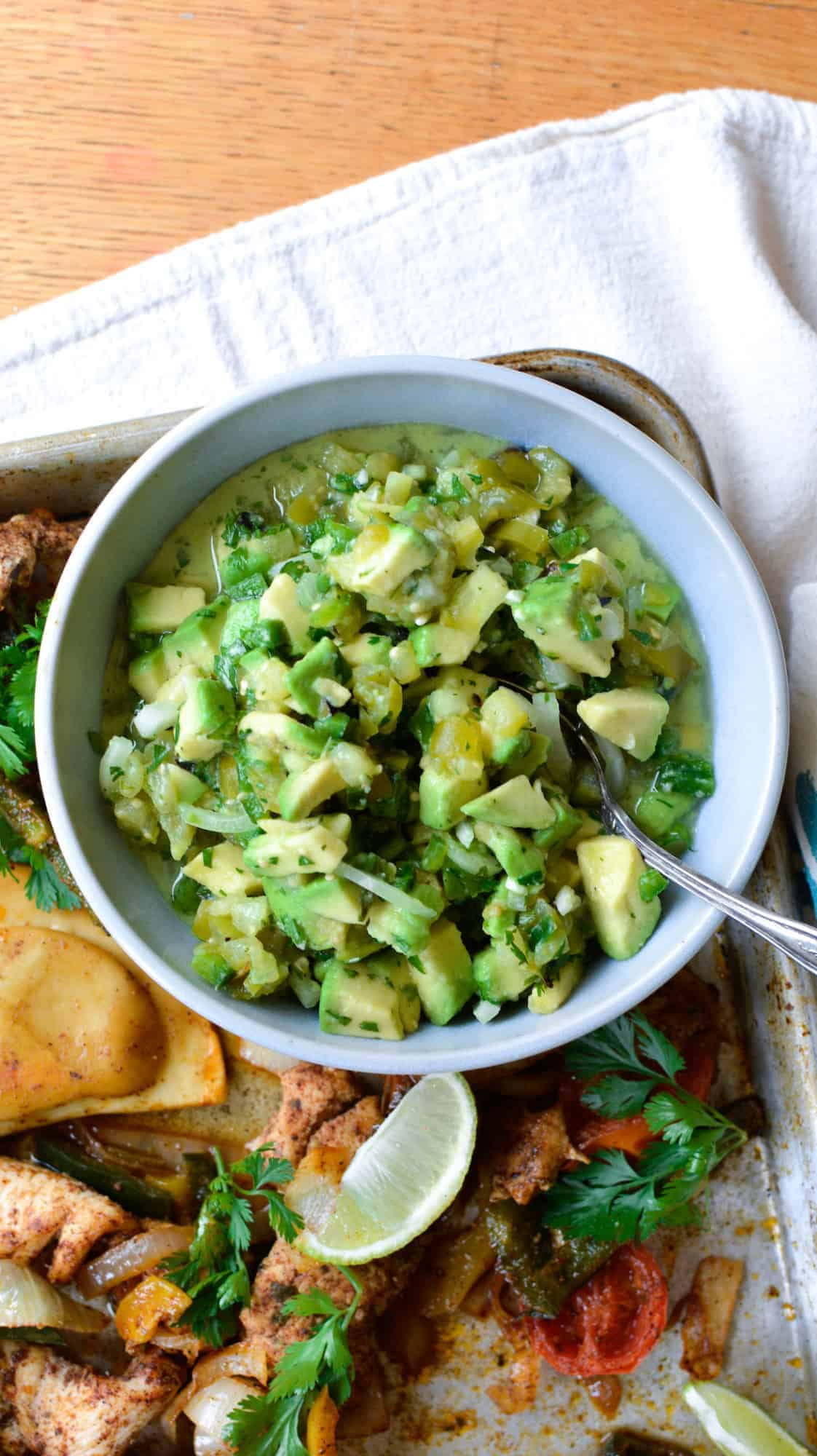 A ceramic bowl filled with tomatillo avocado salsa sitting on a baking sheet with a spoon in the bowl.