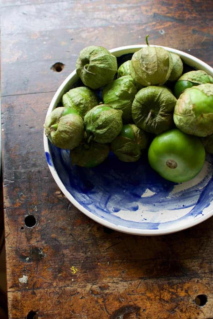 A blue and white dish filled with tomatillos on a wood table.
