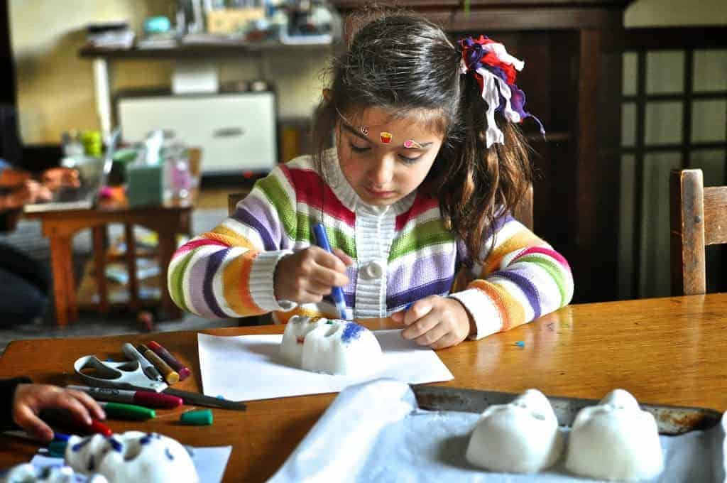 A little girl in a striped sweater sitting at a wood table decorating a sugar skull with blue glitter glue.