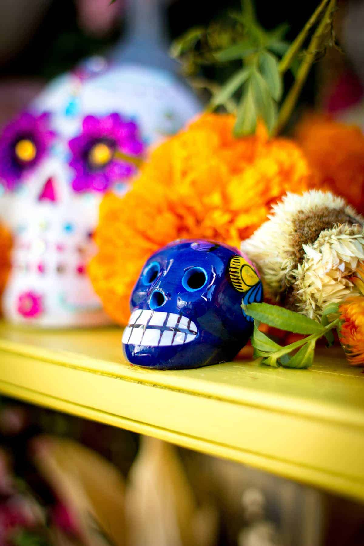 A blue ceramic calavera sitting next to orange marigolds on a Day of the Dead Altar next to a white larger calavera in the background.