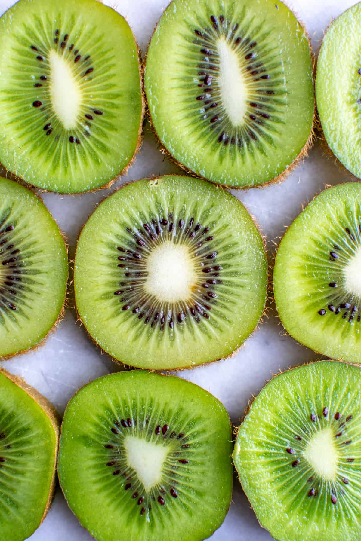 A series of 9 pieces of sliced kiwi all in a line.