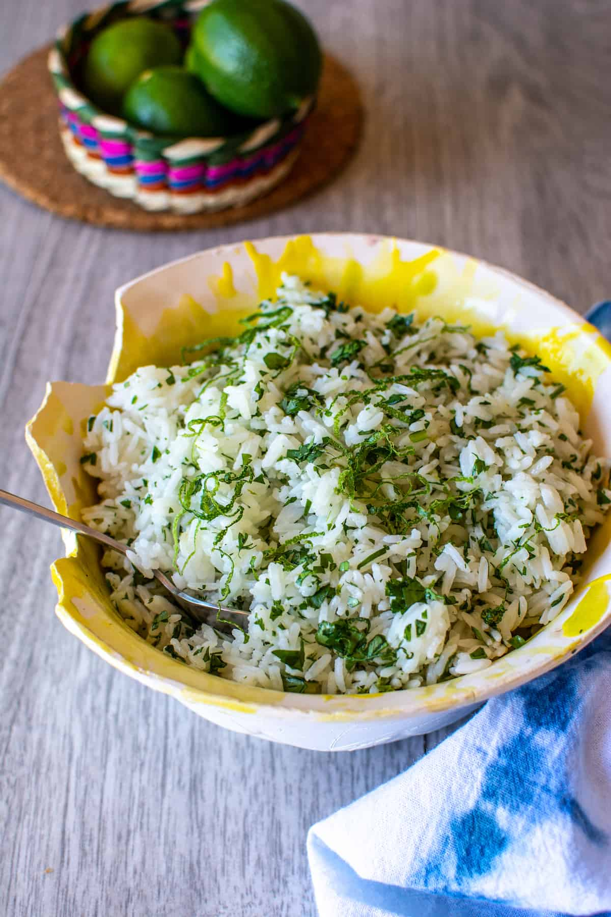 A yellow bowl of cilantro lime rice with a spoon sticking out of one side sitting on a gray table next to a blue and white napkin.
