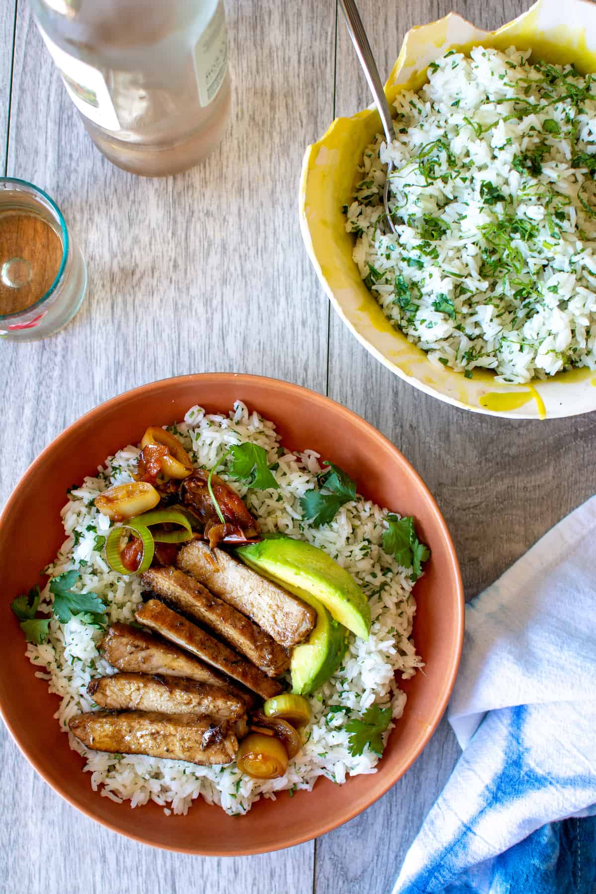A brown bowl with cilantro lime rice, sliced pork chop, sliced avocado and cilantro leaves in it sitting next to a yellow bowl of rice and wine.
