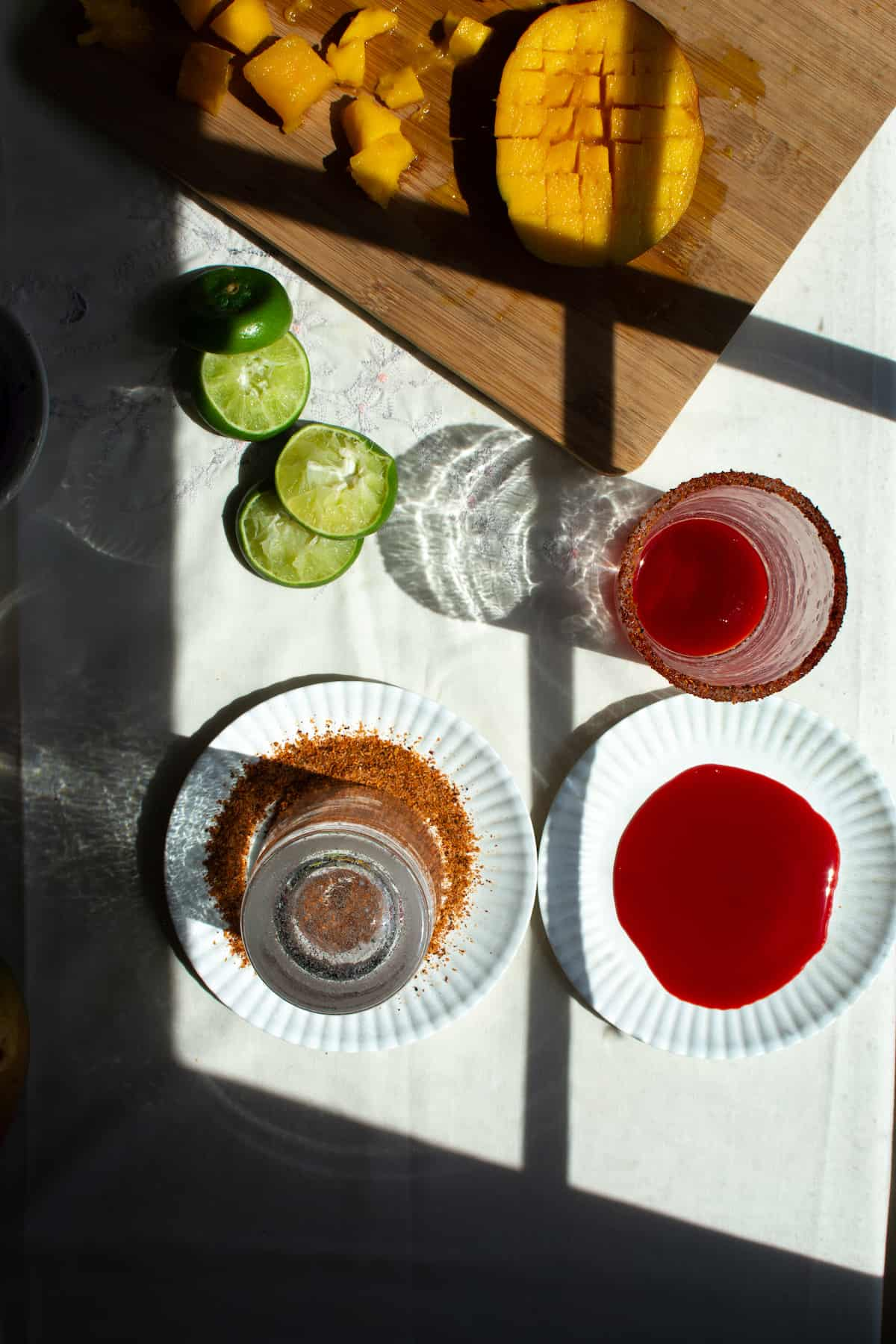 Overhead image of two small plates sitting on a white table with two glasses near them and lime halves.
