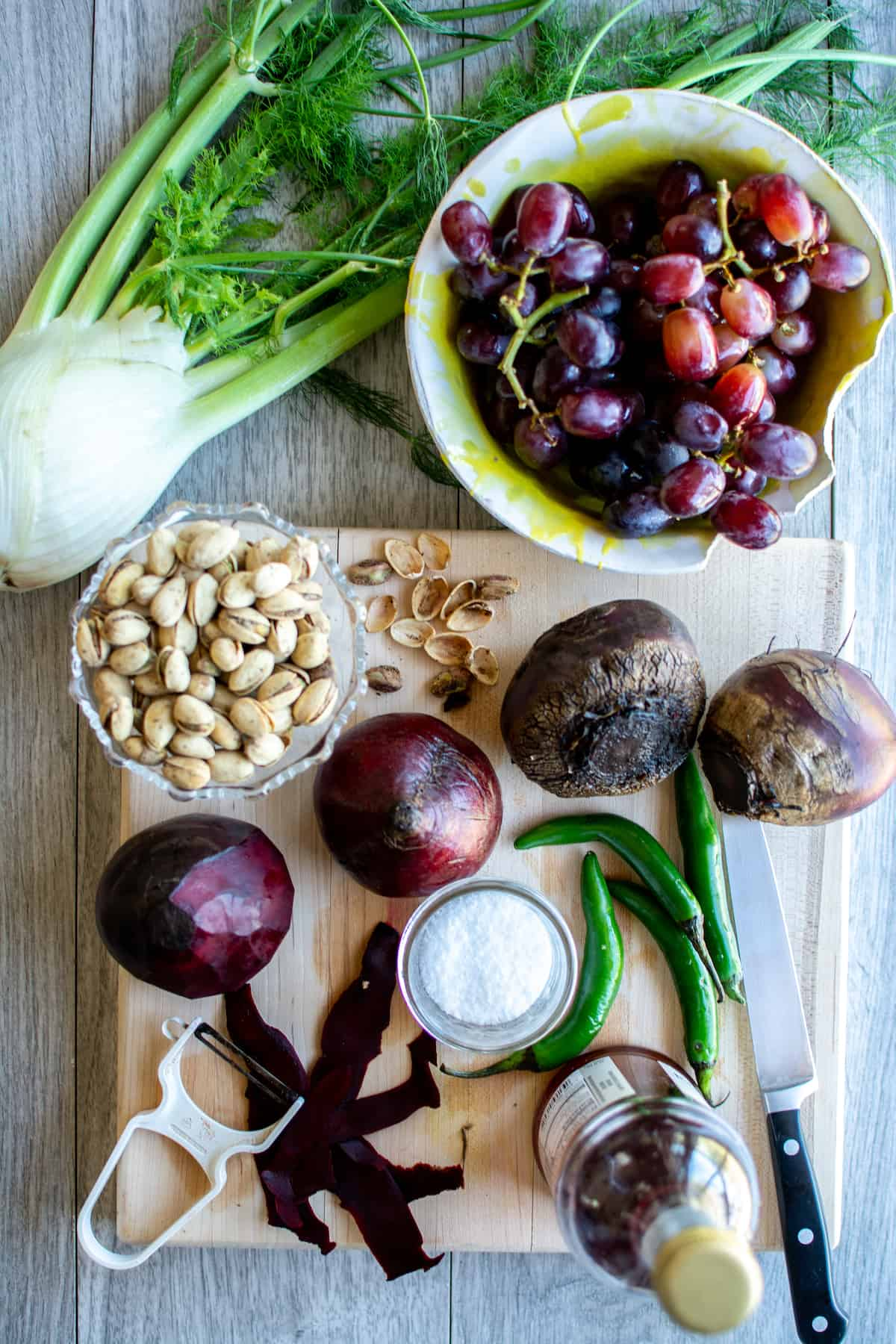 All the ingredients to make this grape-roasted beet salad including, fresh fennel, red grapes, pistachios, red beets, and serrano peppers.