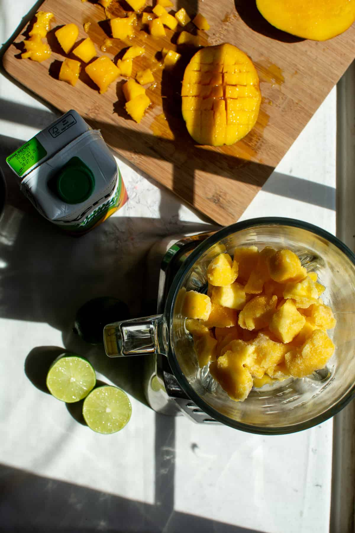 Overhead image of frozen mango chunks in a blender with a lime cut in half sitting next to the blender.