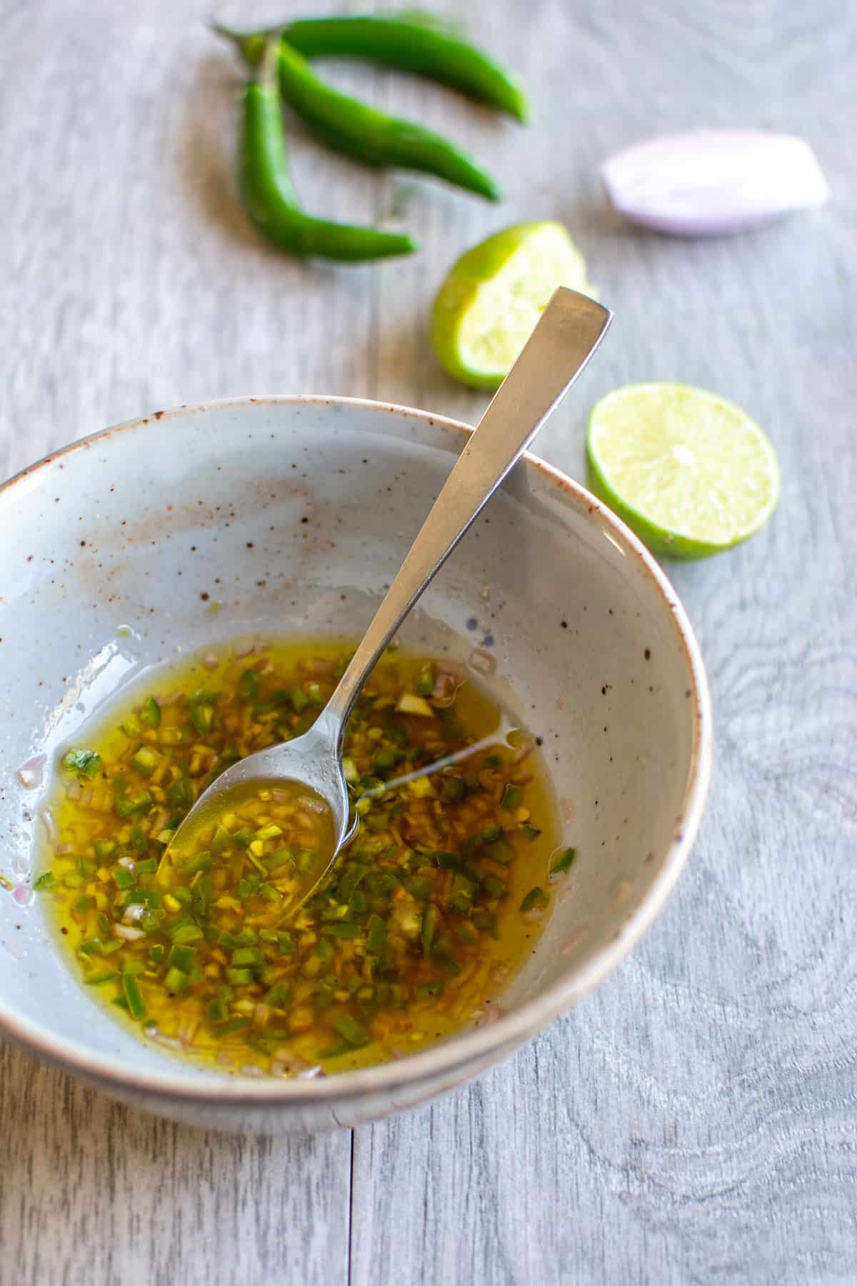 A ceramic bowl with serrano pepper dressing in it and a silver spoon sticking out of one side. Lime halves and serrano peppers behind it.