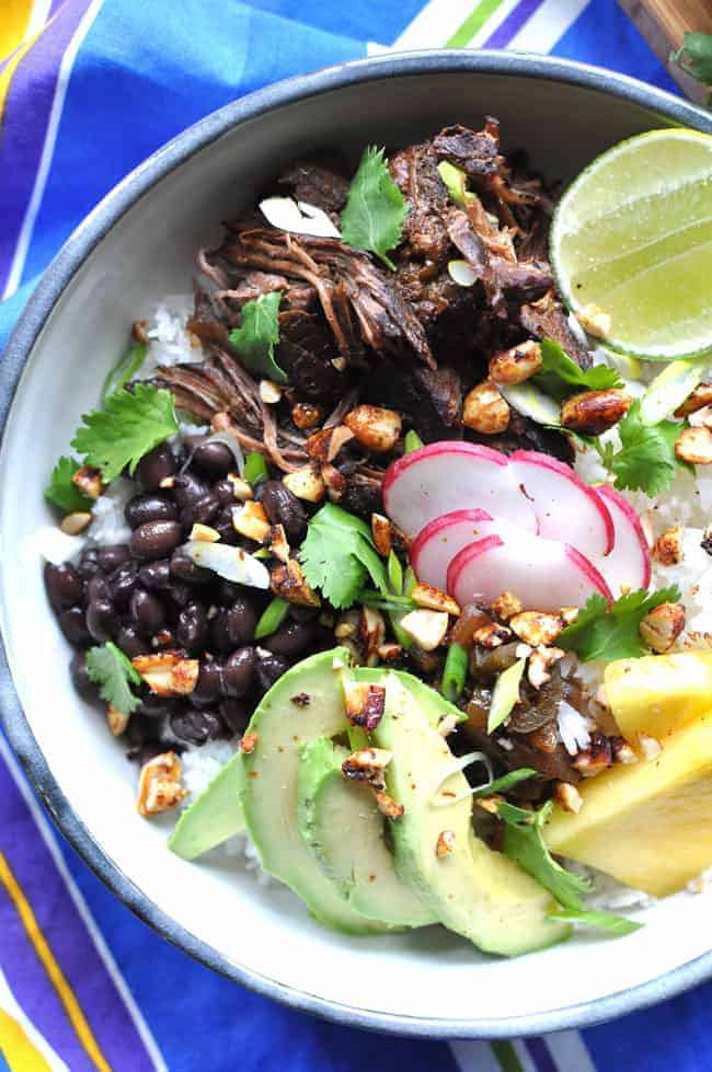 A bowl with black beans, Carne Adobada, avocado slices, radish slices, a half of a lime, and pineapple wedges in it.